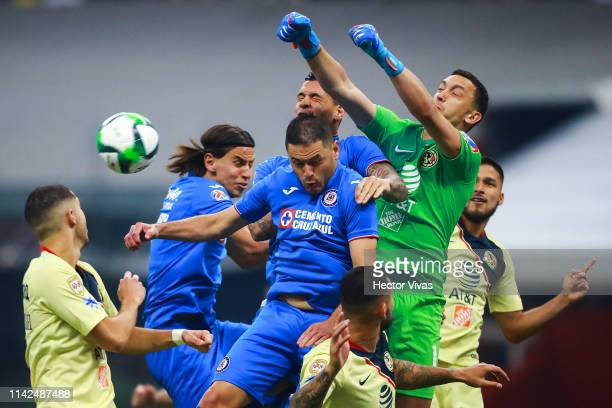 Agustin Marchesin of America struggles for the ball with Igor Lichnovsky Pablo Aguilar and Milton Caraglio of Cruz Azul during the quarterfinals...