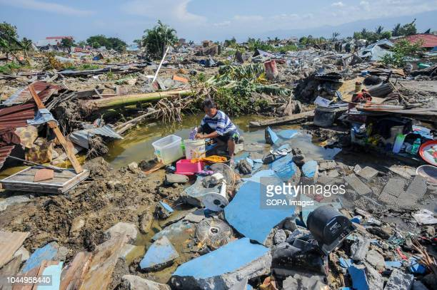 Agustin washing clothes between the ruins of her house in Balaroa village after the earthquake in Palu A deadly earthquake measuring 77 magnitude and...