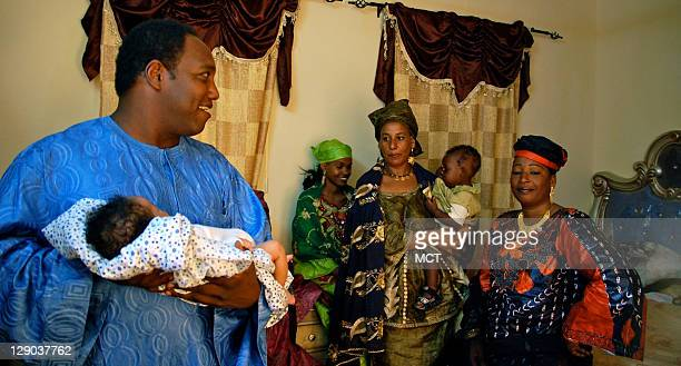 Aha Issufa a prominent Tuareg businessman holds his newborn son next to his wives in Agadez Niger