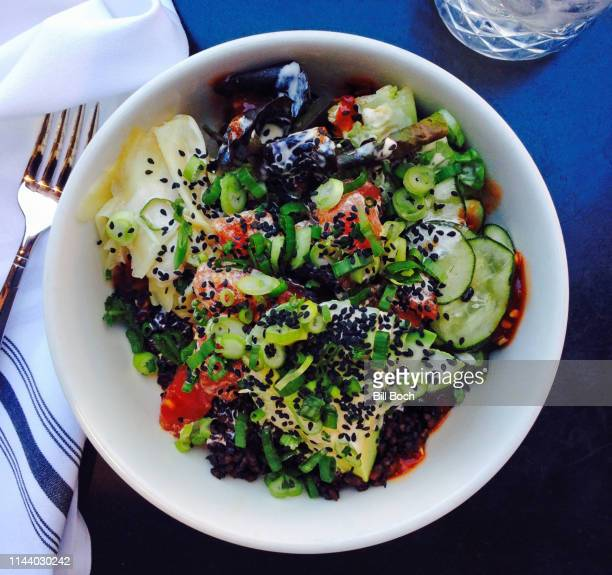 ahi tuna poke style meal in a white bowl with a fork and napkin, on a blue  table with a glass of water - black rice stock pictures, royalty-free photos & images