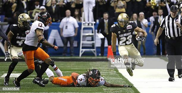 Ahkello Witherspoon of the Colorado Buffaloes leaps over the would be tackle of Ramon Richards of the Oklahoma State Cowboys in the Valero Alamo Bowl...