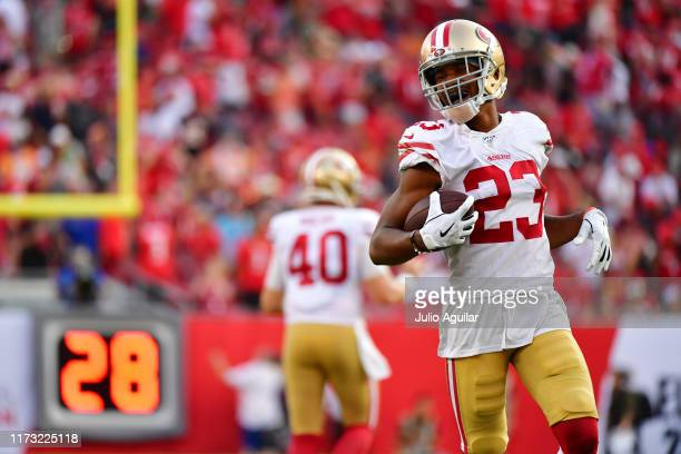 Ahkello Witherspoon of the San Francisco 49ers runs back to the bench after scoring on an interception thrown by Jameis Winston of the Tampa Bay...