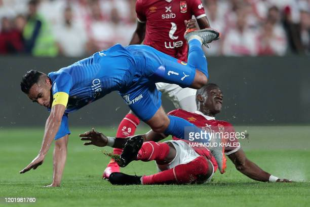TOPSHOT Ahly's midfielder Aliou Dieng tackles Zamalek's defender Hazem Emam during the Egyptian Super Cup final football match between Ahly SC and...