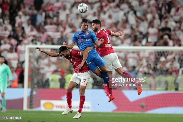 Ahly's midfielder Amr elSolia and defender Yasser Ibrahim vie for a header against Zamalek's forward Mostafa Mohamed during the Egyptian Super Cup...