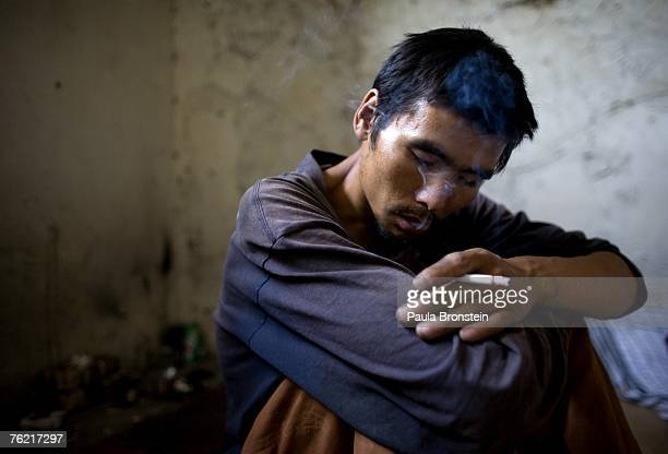 Ahmad a heroin addict smokes a cigarette after getting high in an abandoned building August 21 2007 in Kabul Afghanistan He has been addicted for...