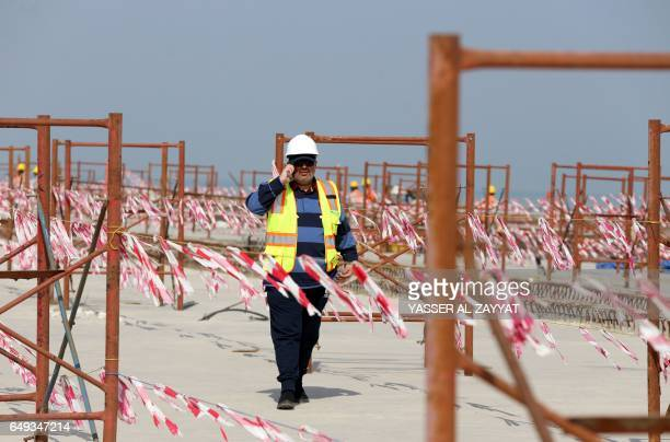 Ahmad AlHassan assistant undersecretary for road engineering at the public works ministry walks at the construction site of the Jaber Causeway in...