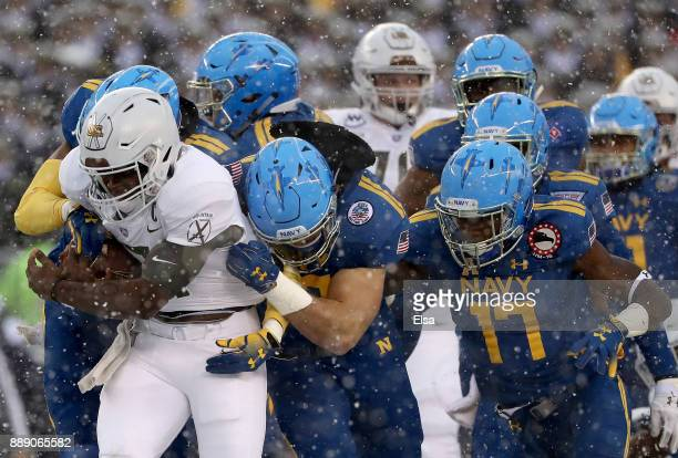 Ahmad Bradshaw of the Army Black Knights is tackled by Tyris Wooten of the Navy Midshipmen and the rest of his teammates on December 9 2017 at...