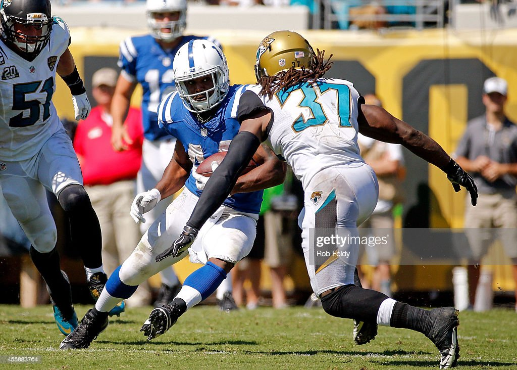 Ahmad Bradshaw #44 of the Indianapolis Colts is defended by Johnathan Cyprien #37 of the Jacksonville Jaguars during the second half of the game at EverBank Field on September 21, 2014 in Jacksonville, Florida.
