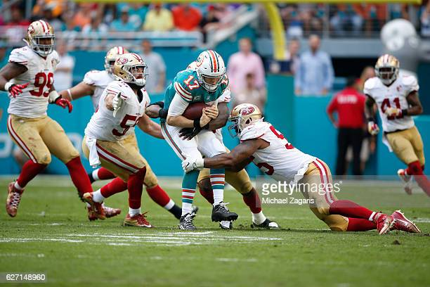 Ahmad Brooks and Gerald Hodges of the San Francisco 49ers sack Ryan Tannehill of the Miami Dolphins during the game at Hard Rock Stadium on November...