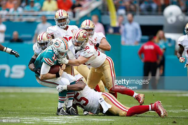 Ahmad Brooks, Nick Bellore and Gerald Hodges of the San Francisco 49ers tackle Ryan Tannehill of the Miami Dolphins during the game at Hard Rock...