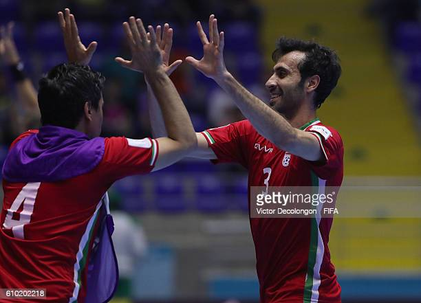 Ahmad Esmaeilpour and Mohammad Keshavarz of Iran celebrate Esmaeilpour's first goal during quarterfinal match play between Paraguay and Iran in the...