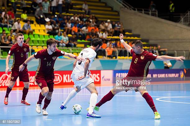 Ahmad Esmaeilpour of Iran controls the ball between Danil Davydov and Eder Lima of Russia during the FIFA Futsal World Cup SemiFinal match between...