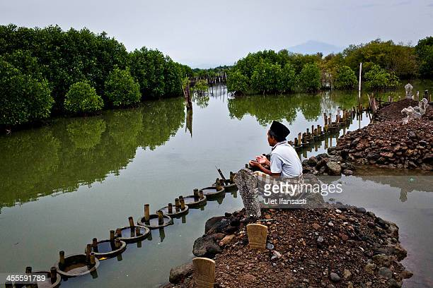 Ahmad Fauzan prays at a public cemetery that is mostly submerged by rising sea levels at Bedono village on December 12 2013 in Demak Central Java...
