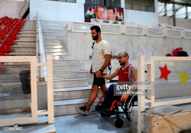 Ahmad Moussa guides his friend Bader al-Hajjami as they set to play basketball at a gymnasium in Syria's capital Damascus, on November 1, 2020. - One...