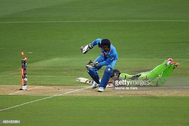 Ahmad Shahzad of Pakistan makes his ground as MS Dhoni of India tries to run him out during the 2015 ICC Cricket World Cup match between India and...