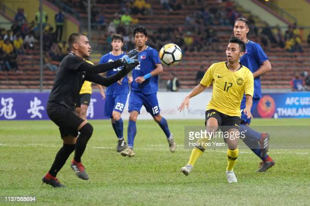 Ahmad Tasnim Fitri of Malaysia and Michael Asong of the Philippines in action during the AFC U23 Championship qualifier between Malaysia and...