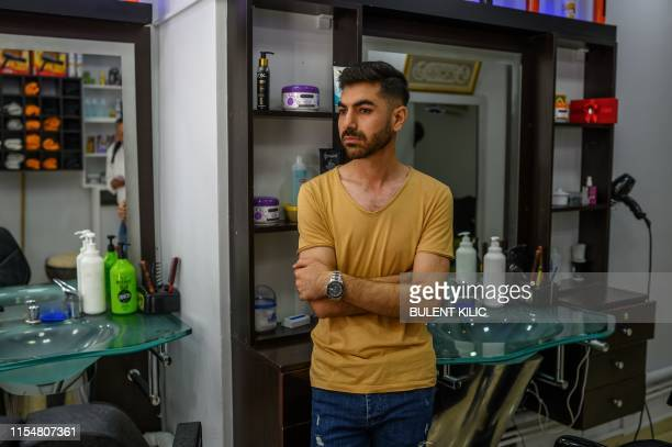 Ahmad Yassine poses for a photo in his barbershop in Istanbul's workingclass district of Kucukcekmece on July 5 2019 The most recent violence against...