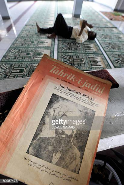 A Ahmadiyah Muslim sect follower rests next to a magazine showing the picture of its founder Gulam Mirza in Jakarta on May 5 2008 Twelve men will...