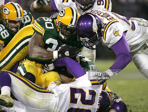 Ahman Green of the Green Bay Packers goes headtohead against EJ Henderson of the Minnesota Vikings as Antoine Winfield hits him low during a game at...