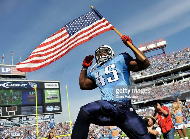 Ahmard Hall of the Tennessee Titans, an armed services veteran, brings out the American flag before a game against the Washington Redskins at LP...