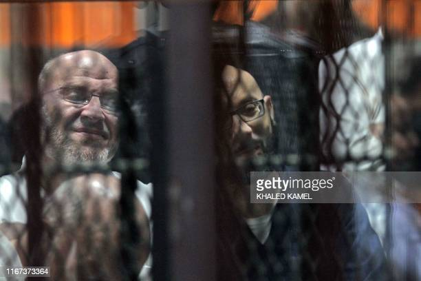 Ahmed Abdel-Ati , ex-chief of staff of Egypt's late ousted president Mohamed Morsi, and Ayman Ali , ex-aide to Morsi, are seen behind bars during a...