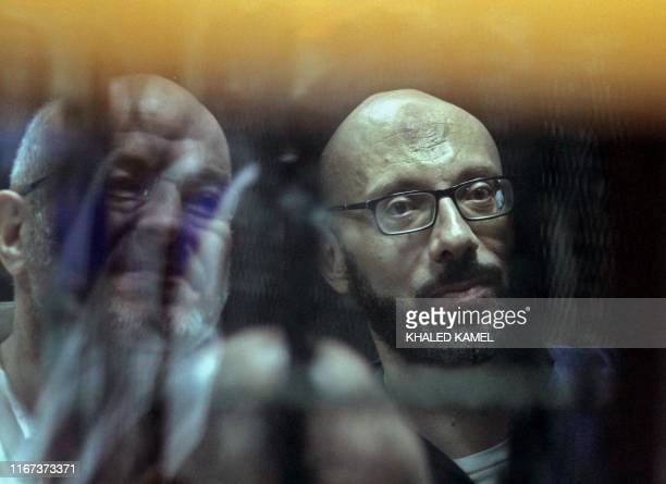 Ahmed Abdel-Ati , ex-chief of staff of Egypt's late ousted president Mohamed Morsi, and Ayman Ali, ex-aide to Morsi, are seen behind bars during a...