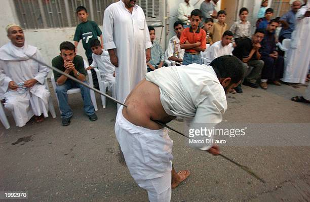 Ahmed Abdul Alftah pierces himself with a metal pole in celebration of the Prophet Mohammed's birthday May 12 2003 in Baghdad Followers of the...