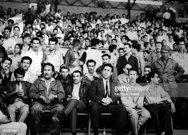 Ahmed Ben Bella attending a meeting at the municipal stadium with Colonel Houari Boumédiène and Commander Ali Mendjili on right and Yacef Saadi and...