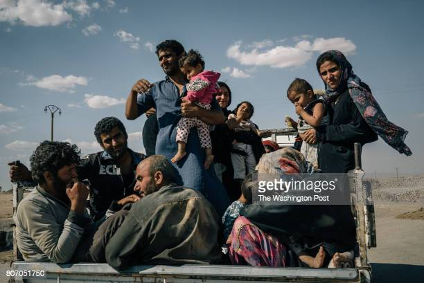 Ahmed Brazu's family sits in the back of a truck after fleeing Raqqa city