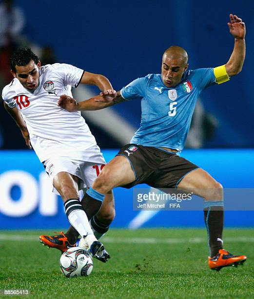Ahmed Eid of Egypt tackles Fabio Cannavaro of Italy during the FIFA Confederations Cup match between Egypt and Italy at Ellis Park Stadium on June 17...