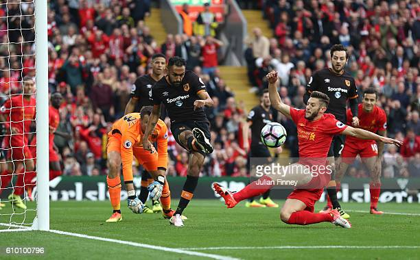 Ahmed Elmohamady of Hull City clears the ball while under pressure Adam Lallana of Liverpool during the Premier League match between Liverpool and...