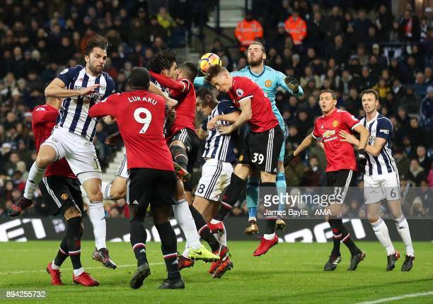 Ahmed Hegazy and Gareth Barry of West Bromwich Albion compete at a corner with David De Gea of Manchester United during the Premier League match...