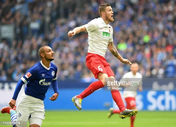 Ahmed Kutucu of Schalke 04 and Jeffrey Gouweleeuw of FC Augsburg battle for the ball during the Bundesliga match between FC Schalke 04 and FC...