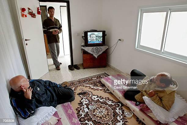 Ahmed Mahajli an Israeli Arab resident of the village of Musmus and his visiting relative Yussef Mahajli watch Israeli television reports of the...