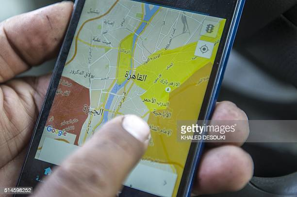 Ahmed Mahmoud an Egyptian driver working for Uber Transportation Company in Egypt checks a map on his phone on February 23 2016 in Cairo The use of...