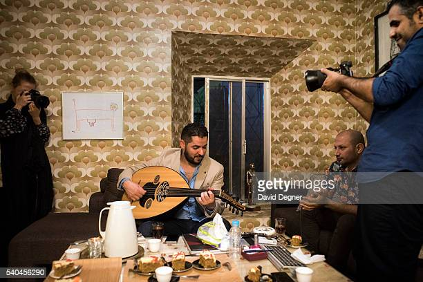 Ahmed Mater right tries out a new lens on guests at his studio on April 05 2016 in Jeddah Saudi Arabia Ahmed is an artistic photographer based in...