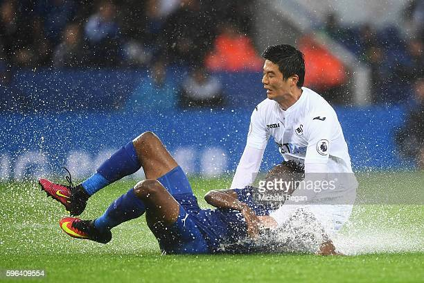 Ahmed Musa of Leicester City and Ki SungYueng of Swansea City battle for possession on the floor during the Premier League match between Leicester...