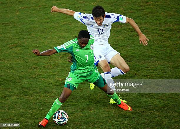 Ahmed Musa of Nigeria and Mensur Mujdza of Bosnia and Herzegovina compete for the ball during the 2014 FIFA World Cup Group F match between Nigeria...