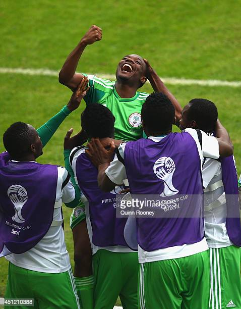 Ahmed Musa of Nigeria jumps into the arms of teammates celebrating his team's second goal and his second of the game during the 2014 FIFA World Cup...
