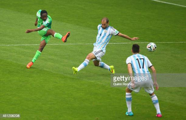 Ahmed Musa of Nigeria shoots and scores his team's first goal against Pablo Zabaleta of Argentina during the 2014 FIFA World Cup Brazil Group F match...