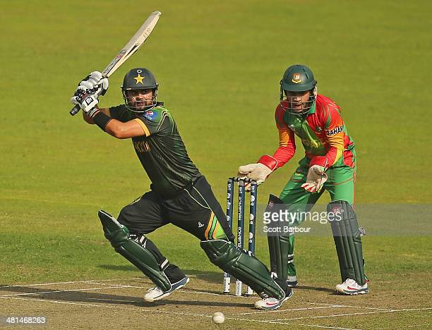 Ahmed Shehzad of Pakistan bats as Mushfiqur Rahim of Bangladesh looks on during the ICC World Twenty20 Bangladesh 2014 match between Pakistan and...