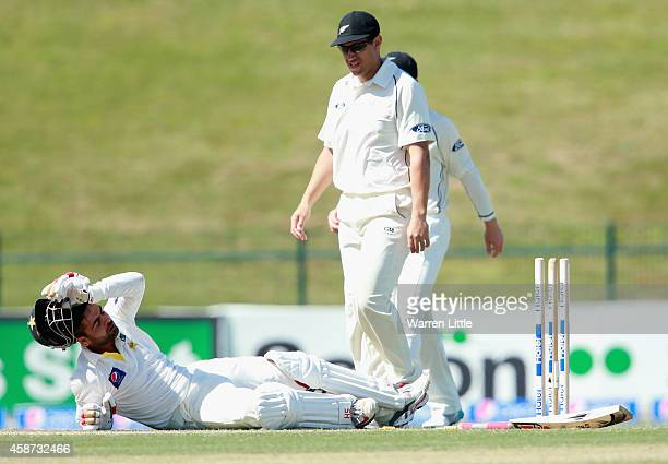 Ahmed Shehzad of Pakistan lies injured after hitting his wicket bowled by Corey Anderson of New Zealand during day two of the first test between...