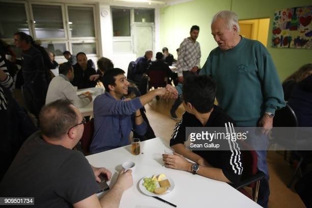 Ahmed Tammaz from Syria shakes hands with German pensioner Kurt Remke during a weekly 'Sprechcafe' meetup of locals and refugees at a community...