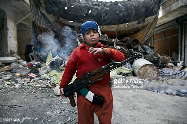 Ahmed the 8yearold son of a Free Syrian Army fighter stands in front of a barricade were he assists Free Syrian Army fighters in the neighborhood of...