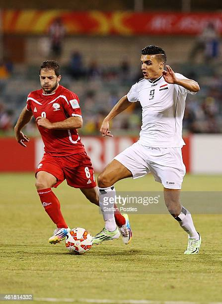 Ahmed Yaseen Gheni of Iraq and Hisham Salhi of Palestine contest possession during the 2015 Asian Cup match between Iraq and Palestine at Canberra...