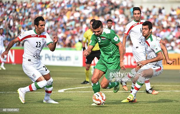 Ahmed Yaseen Gheni of Iraq beats Mehrdad Pooladi and Morteza Pouraliganji of Iran during their AFC Asian Cup quarterfinal football match in Canberra...