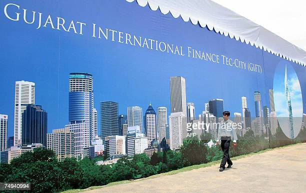 An Indian pedestrian walks past a poster advertising The Gujarat International Finance TecCity [GIFT] Exposition at Tagore Hall in Ahmedabad 28 June...