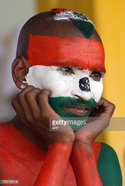 Indian cricket supporter Sudhirkumar Gautam his face and torso painted with the Indian tricolour watches from the stands during the ICC Champions...