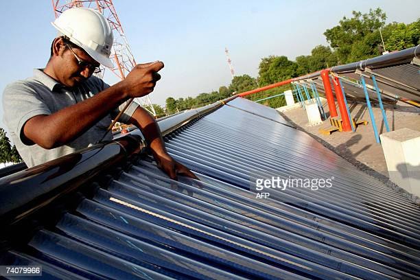 Manish Verma, Service Engineer does maintenance work on tube solar collectors at Mamata Energy Limited on the Rakanpur-Santej road nearly 25 kms from...