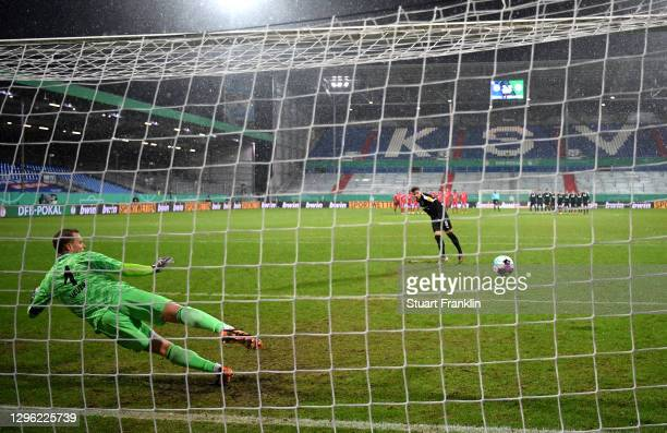 Ahmet Arslan of Holstein Kiel scores past Manuel Neuer of Bayern Munich in the shootout during the DFB Cup second round match between Holstein Kiel...